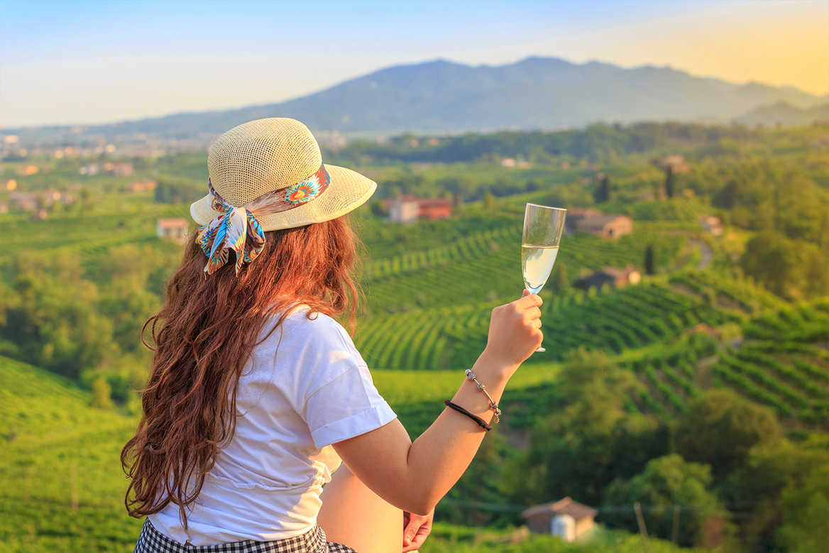Woman sips white wine in Italy