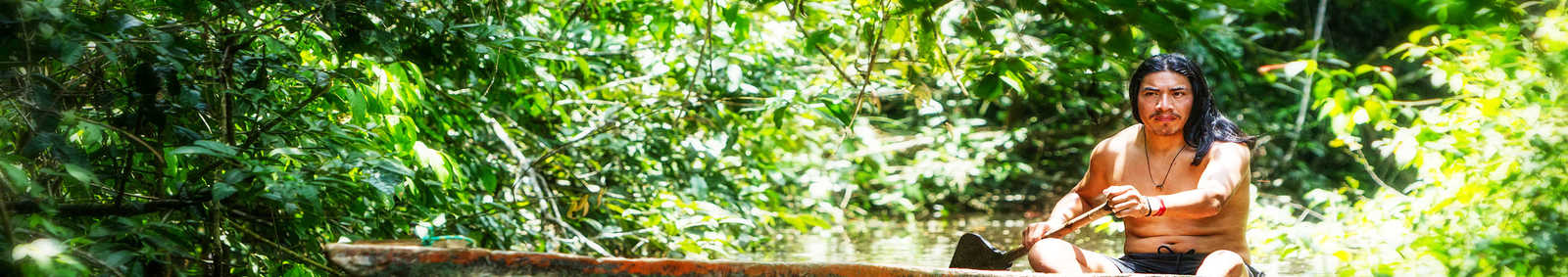 Indigenous man canoeing through the Amazon jungle, Ecuador