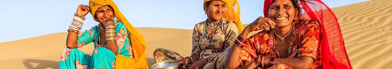 women sitting at the sandy desert