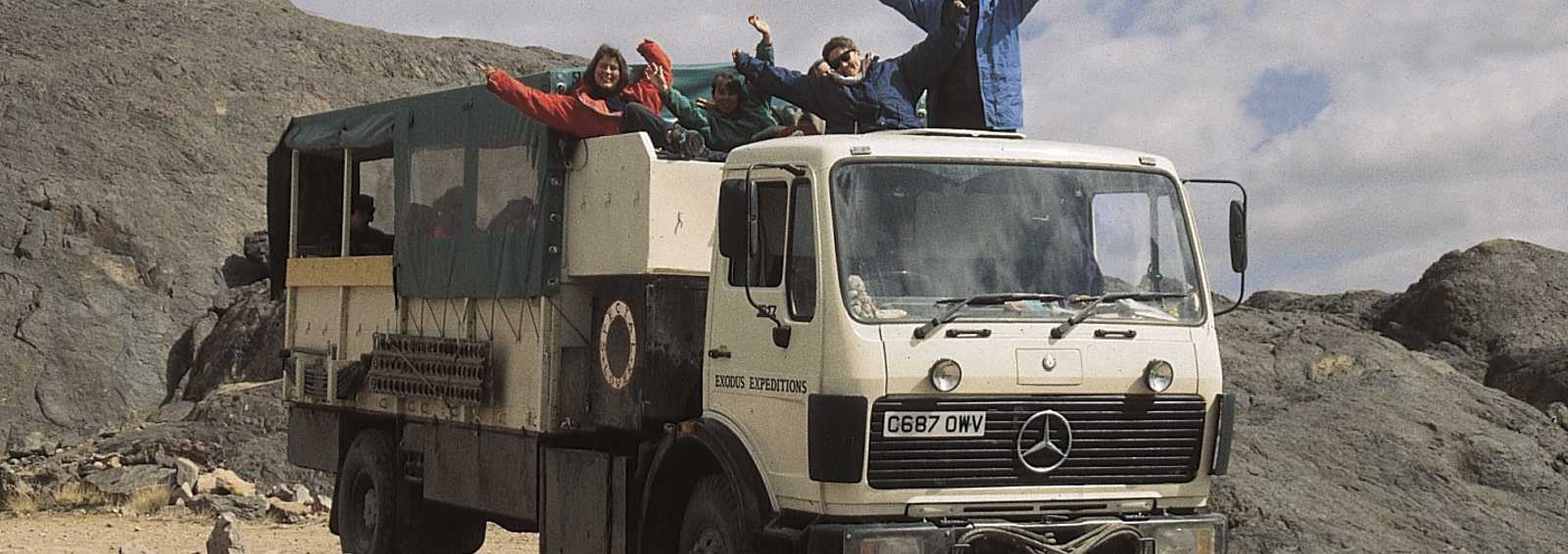 Overland truck in Namib desert, happy clients in 'dog' box