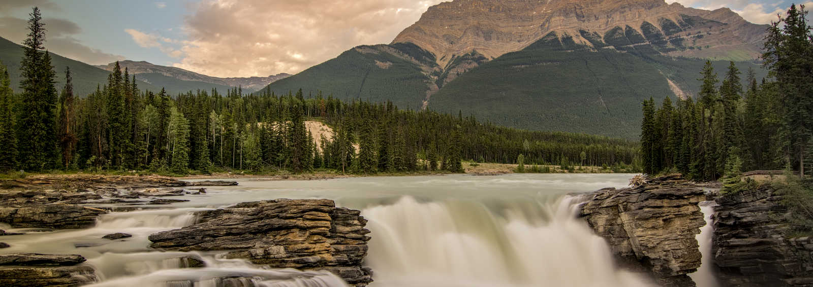 Long exposure of the beautiful Athabasca Falls with towering sunlit of Mount Kerkeslin in the background
