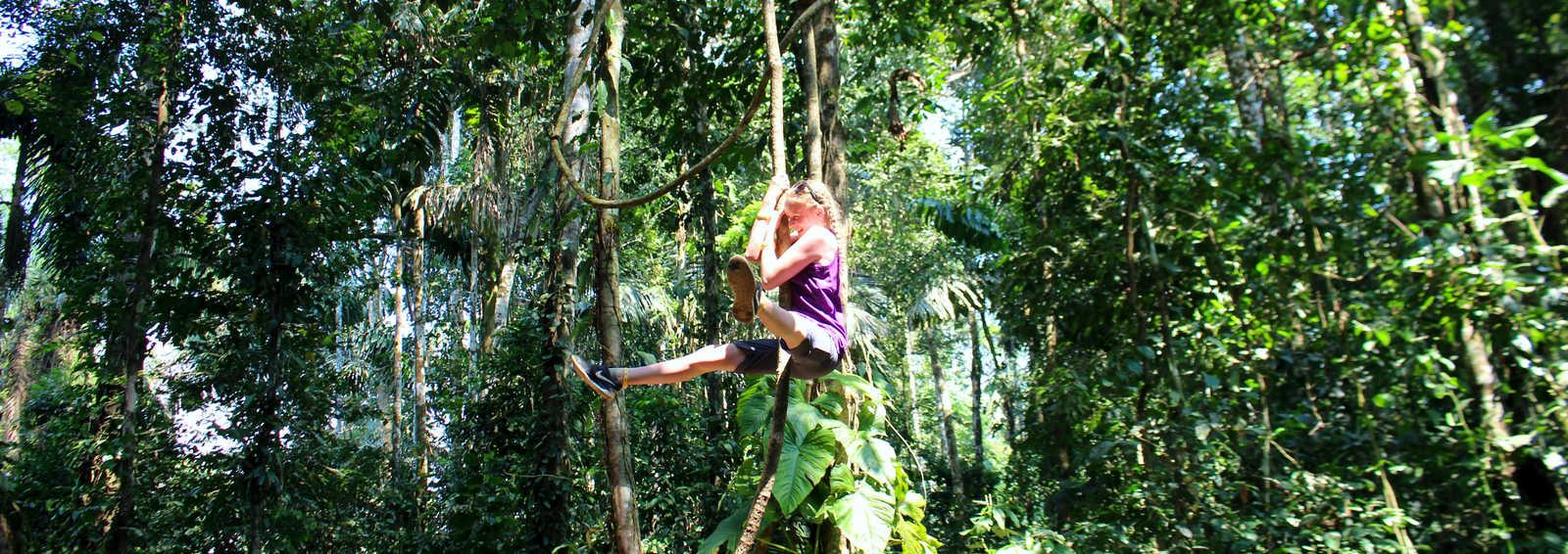 Girl swinging in the trees, Amazon, Peru