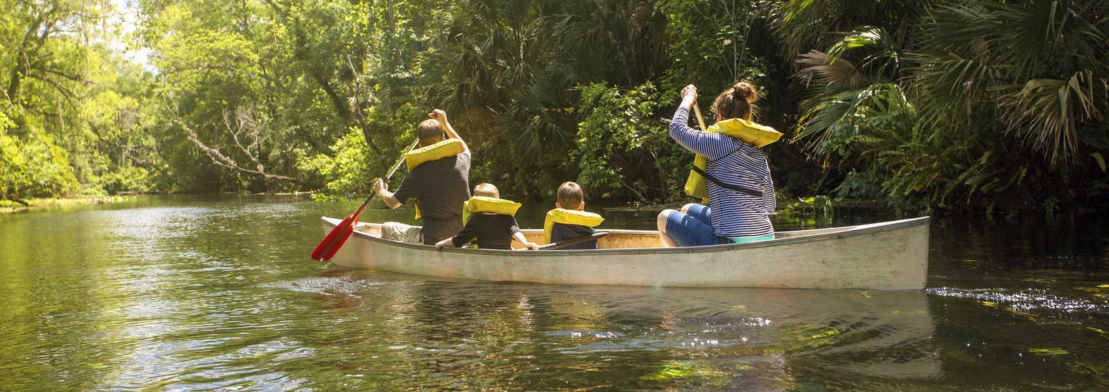 Family canoe ride down a beautiful tropical river
