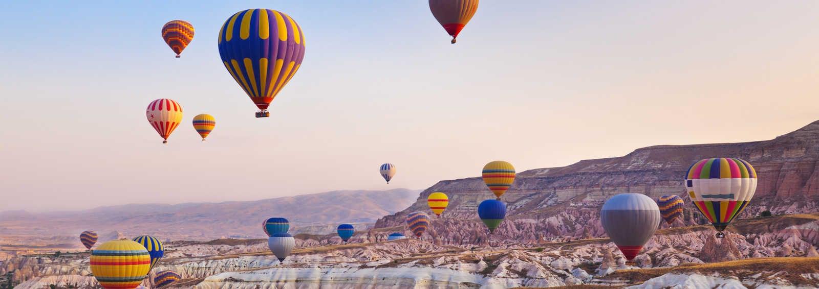 Hot air balloon flying over rock landscape at Cappadocia, Turkey