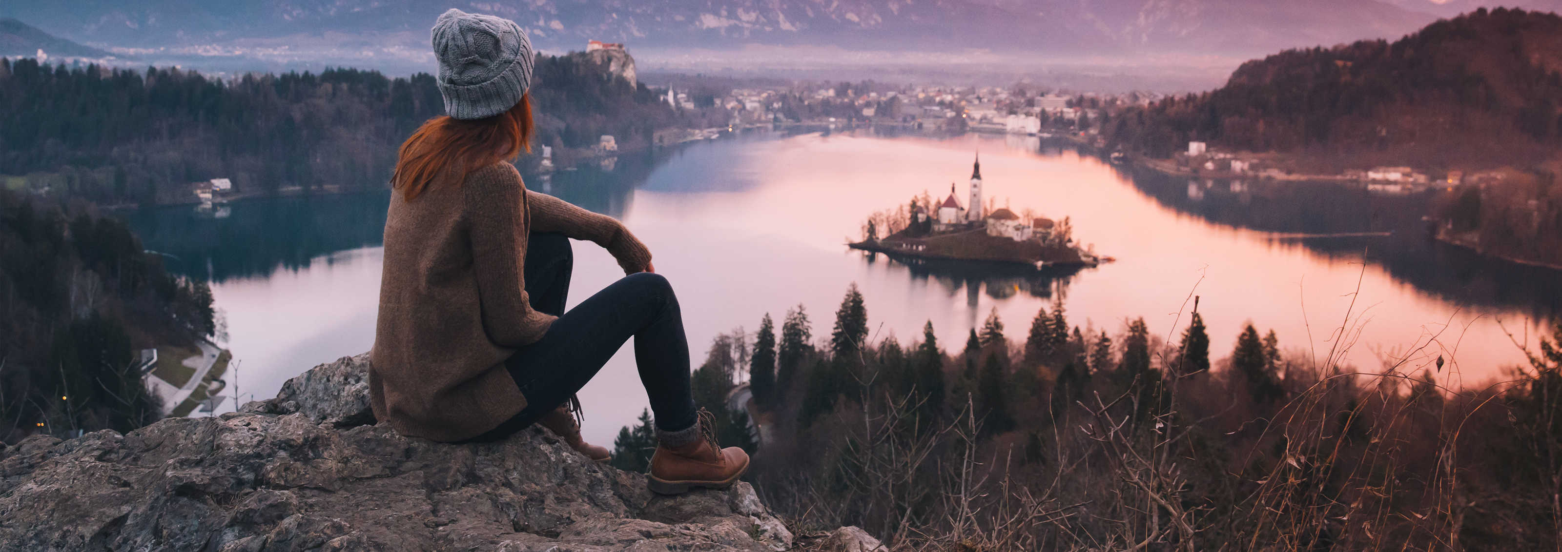 Woman looking on Bled Lake with Island, Castle and Alps Mountain on background.