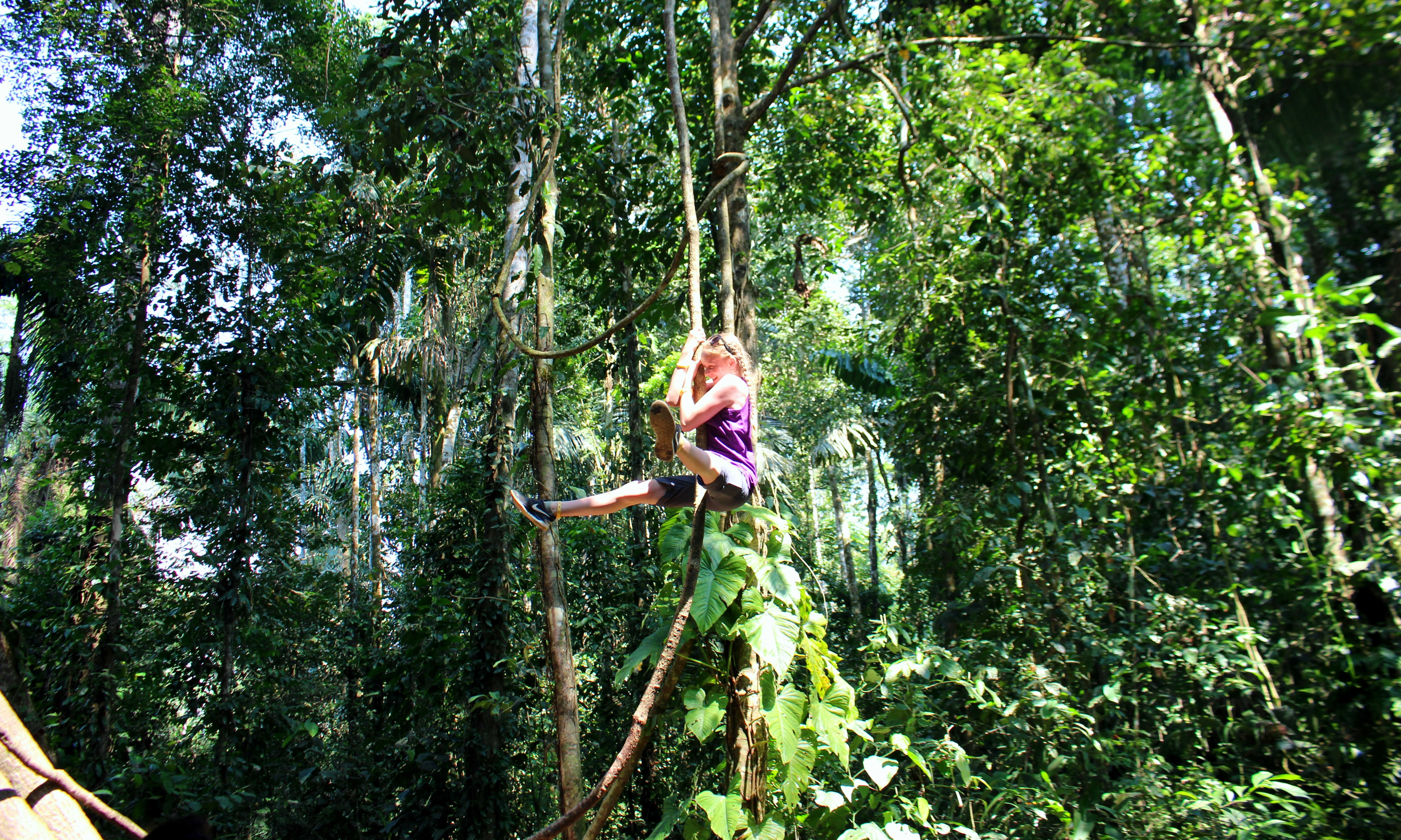 Young girl playing Tarzan in the Amazon, Peru